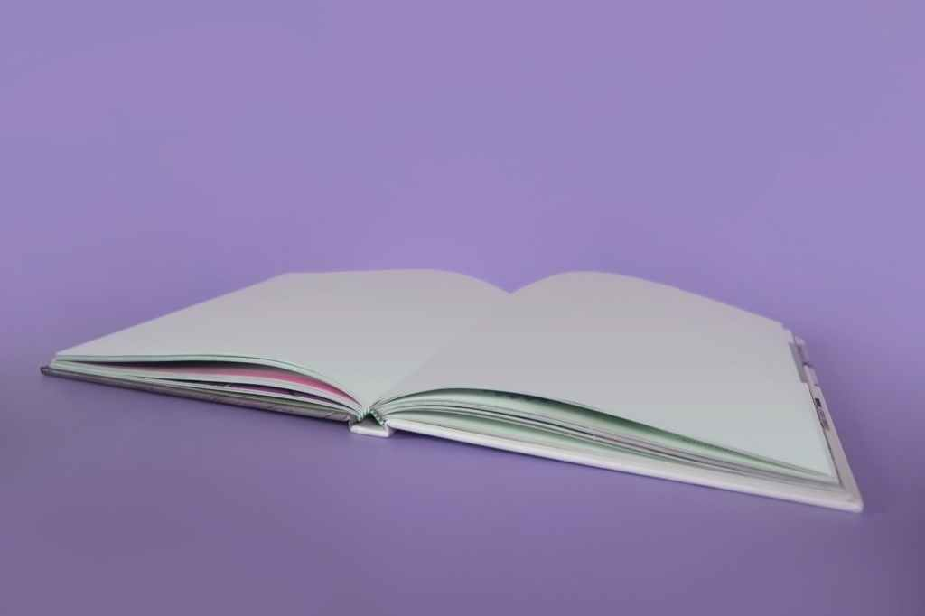 open book on purple background. there is no text on the pages. image courtesy of @designecologist on pexels.com