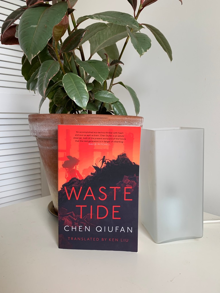 "image of chen qiufan's book ""waste tide"" on a table with a white lamp and a potted plant"