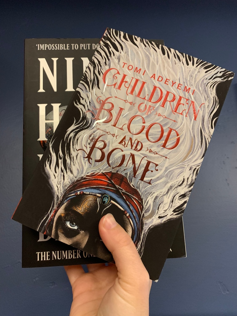 "image of leigh bardugo's book ""ninth house"" behind tomi adeyemi's book ""children of blood and bone"""