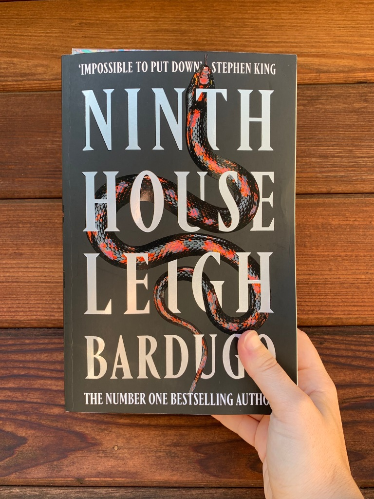 "image of leigh bardugo's book ""ninth house"" with the paperback alternative cover image with a red and black snake"