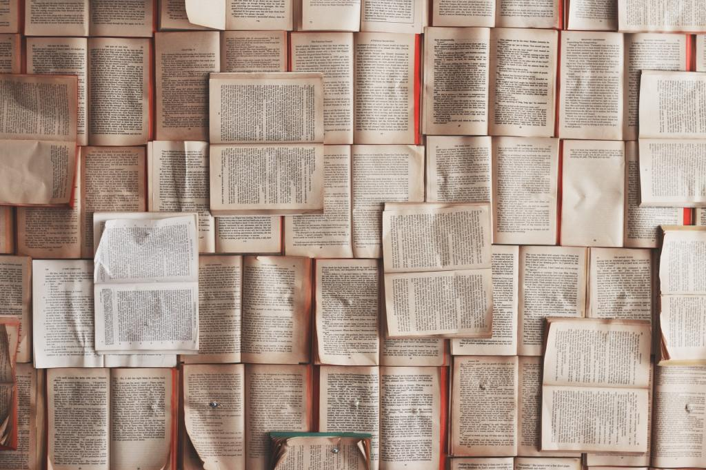 image of dozens of book lying open, showing interior text facing up all puzzle-pieced together to form a single, flat wall. image from Patrick Tomasso on Unsplash.